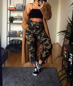 Baddie Fall outfit: camo pants with a black crop top and beige long coat and black vans. Fall outfit idea, baddie outfit inspo.