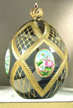 "(3) FABERGE eggs__Theo Faberge ""Four Seasons Egg"" As its name suggests the Four Seasons Egg portrays the individual character of the year's seasons. Spring, Summer, Fall and Winter represented in rich hand painted enamels,each in an elegant oval panel. Spectacular in 24% hand cut lead crystal and adorned with hand painted 23 karat gold. The vermeil Imperial Crown is set with a fine cabochon ruby."