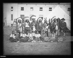 Group portrait of 14 adults and 2 children of the Rosebud Sioux tribe standing outside of the Indian School building at the St Louis Fair at the Louisiana Purchase Exposition, St Louis, Missouri, June 6, 1904.
