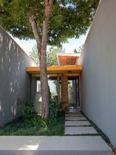 Boas-vindas. O percurso até a entrada social tem placas (90 x 90 cm) de porcelanato antiderrapante (Portinari). A pequena laje que avança acima da porta ganhou destaquecom tinta acrílica amarela (Suvinil).