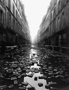 Library books floating down a street during the Great Flood of Paris, 1910.