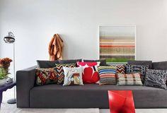 sofá cinza e muitas almofadas coloridas