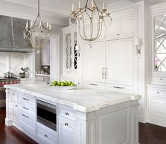 Built-in refrigerator - mirrored cabinets - chandeliers over island - white painted cabinets - grey painted island - marble countertops .: O'Brien Harris :.
