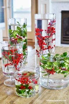 Festive Floating Flora: This vivid centerpiece will take you just a few minutes. Simply fill various jars with water — stop just a few inches below the brim — and add American and Michigan holly. Purchase floating candles for a warm bonus. Click through for more DIY Christmas centerpieces you'll love!