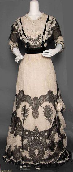 "Кружевное платье для обедов, ок. 1902 г. Augusta Auctions. WHITE & BLACK LACE DINNER GOWN, c. 1902. 1-piece, cream Valenciennes lace w/ black chantilly lace swags on bodice & lower hem, princess lines, scoop neck, short sleeves, bodice w/ jet & turquoise beads & jet ovals, B 36"", W 26"", H 40"", L 63""-72"", (taffeta lining shredded) very good. Suddon-Cleaver Collection, Toronto."