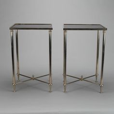 Pair Metal Tables With X-Form Stretchers and Black Glass Tops  --  Pair of circa 1960s small square accent tables found in France feature classically styled details including silver tone finish, reeded legs, and criss-cross X-form stretchers topped with finials. Table tops are black glass. Sold and priced as a pair.  --   Item:  7167  --  Retail Price:  $2895