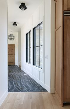 Benjamin Moore Simply White The back entry features a stone herringbone floor tile and board and batten walls painted in Benjamin Moore Simply … – Mudroom Style At Home, Home Renovation, Home Remodeling, Planchers En Chevrons, Flur Design, Tile Design, Wood Design, Hill Interiors, Design Interiors