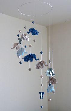 Mobile bébé en Origami Eléphants et Etoiles, effet en spirale.  Composition : - 11 Origami Eléphants, à motifs, couleurs bleu marine, gris clair, taupe et blanc. - 22 Origami Etoiles chinoises du bonheur  Dimensions : Longueur : 60 cm environ (+30 cm de suspension) Largeur : 20 cm environ Chaque éléphant fait 5cm, et chaque étoile 1.5cm Le mobile se suspend au plafond par une boucle en fil nylon.  Matériaux : papier origami, fil de nylon, perles de fixation, cercle métallique.  Ce mobile…