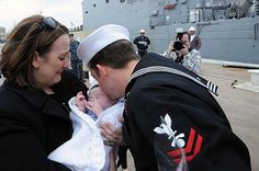 120310-N-TC587-041 MAYPORT, Fla. (Mar. 10, 2012) Interior Communications Electrician 2nd Class Bradley Laroche kisses his newborn daughter for the first time during a homecoming celebration for the guided-missile frigate USS De Wert (FFG 45) at Naval Station Mayport. De Wert completed a seven-month piracy deployment to the Horn of Africa and Indian Ocean. (U.S. Navy photo by Mass Communication Specialist Seaman Apprentice Damian Berg/Released)