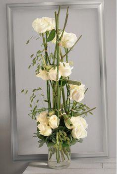 Plume Blanche: Bouquet linéaire vertical de roses blanches gros boutons sur une structure de branchage vert et feuillage aérien.