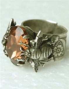A magnificent beveled amber stone conjures thoughts of sweet nectar, mounted upon an intricate bumblebee casting.