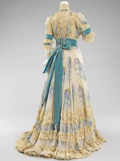 Afternoon Dress - Jacques Doucet, 1903 : This is an elegant afternoon dress that would be suitable for afternoon events, such as the races and other promenade activities. The dress is an excellent example of Doucet's penchant for lingerie-like garments, which is represented by the delicate ruffles and rose printed chiffon. The color combination of blues accented with turquoise is a favorite of the designer.