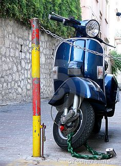 A classic modern Vespa Italian scooter parked on a narrow street in Italy