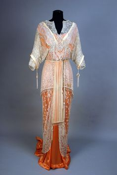 FRENCH BELLE EPOCH TRAINED and CRYSTAL BEAD ENCRUSTED GOWN,  1910-1914, Tangerine silk satin, weighted fish tail hem, attached two layer short sleeved overdress of white net with crystal and mother of pearl beads, outer sleeves with beaded tassel and ring drops, matching drops at end of chiffon panel set in cutaway skirt front, shorter net layer fringed.