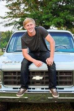 sitting on the hood of his truck for senior picture