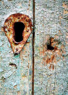 Rusty escutcheon on weathered wood with peeling paint