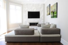 Family Room designed by Enviable Designs - Accent wall made up of marble slab with mosaic tiles encompassing the fireplace. Tone on tone contemporary furnishings for family and friends to lounge. Nature painting hung on walls to bring nature into the space.