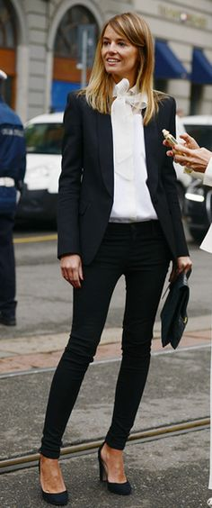 Black blazer, white blouse with a bow, black trousers, and black heels