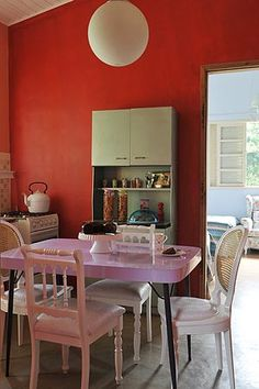 As paredes da cozinha receberam pintura com tinta cor vermelho-pimentão. O armário de aço verde-claro, dos anos 1950, a mesa de Formica lilás, dos anos 1960, e as cadeiras antigas