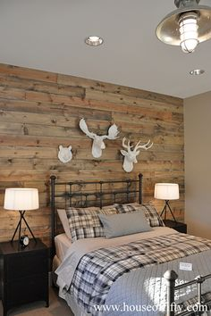 Rustic cabin style bedroom with reclaimed wood planked wall featuring a trio of faux taxidermy wildlife over iron bed dressed with gray sheets layered alongside gray and black plaid bedding and a gray coverlet with matching pillow sham.