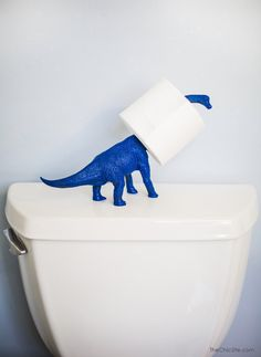 Use a dinosaur toy to hold an extra toilet paper roll.