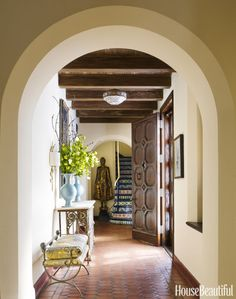 A 19th-century Cambodian sculpture sets an exotic tone in the foyer of a Richmond, Virginia, Spanish Colonial Revival house, recently decorated by Lili O'Brien and Leigh Anne Muse. The antique bench is covered in a Dogwood Fabrics batik. The mirror is from Marston Luce Antiques.