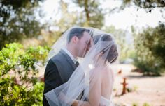 Bride and groom under the veil kiss