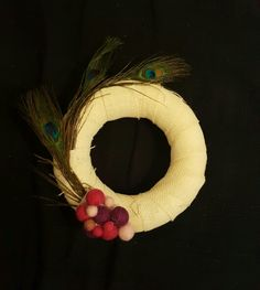 Wreath 24cm, with white sack, nepal wool and peacock feathers. Wreath with blue ribbon, blue and gold satin decorative band ribbon , peacock feathers and nepal felt balls. I used 24cm yarn and hot glue to glue the white sack ribbon over the yarn.Then I put the peacock feathers and the nepal felt balls over them for more spring touch.I wrote a card with lots of congratulations wishes for my collagues PhD and gave it to her as a complement gift.