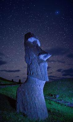 """Uma antiga estátua Moai observa a noite estrelada. """"As estátuas andaram!"""", diziam os moradores da Ilha de Páscoa. Arqueólogos ainda tentam entender como --e se a fábula era uma advertência de desastre ambiental ou celebração da perspicácia humana"""