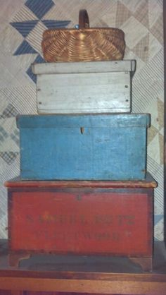 "Antique stack of boxes.  Bottom in old red is a small blanket chest with owners name ""Samuel Kutz Fleetwood"". On top is small old blue painted box with a wrap around edge top, next is a box much like blue, smaller in old gray.  Topped off with a sweet melon basket"