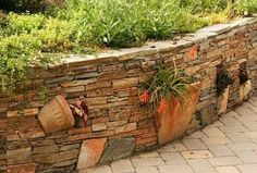 Example of incorporating broken pots into a narrow stone wall and using them as planters.