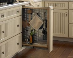 Pullout Perforated Organizer with Hooks  Who doesn't have a wasted nook in between cabinets? I love this idea for hanging kitchen utensils.