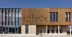 SIGN DESIGN IDEA - Integrate A Logo Into The Exterior Of A Building - The building, located in Edinburgh, Scotland, is covered in timber cladding, and a section of the wood was cut out in the shape of the logo, making the name visible for people to see from the surrounding area.