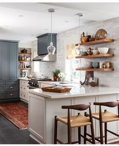 Beautiful kitchen with open shelving and subway tile.