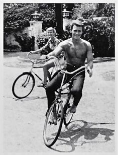 Photo of bare chested Clint Eastwood rambling on a bike. 1960