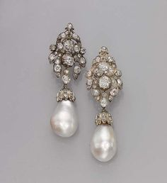 A pair of antique diamond and natural saltwater pearl earrings. Each suspending a detachable drop-shaped natural pearl from an old-cut diamond surmount, surmounts circa 1880.