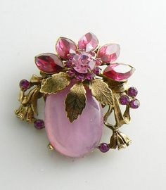 Golden Leaves, Pink Rhinestones and a Pink Glass Cabochon. Set in gold tone metal. Marquise rhinestones act as flower petals. Measures 2. Very good condition. Very pretty brooch.