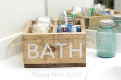 DIY wood caddy used as an organizer for the bathroom. With fun rope handles and stenciled letter, this is a really easy and stylish DIY project with a nautical feel.