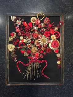 This is a jewelry art handmade recycled jewelry art red flower bouquet. First I glue black felt on cardboard backing and then securely glue the jewelry on the fabric. The jewelry ranges from contemporary to vintage. I use beads, trinkets, charms, rhinestones, and chains from
