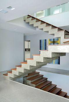 Escada | Os três pavimentos são conectados pelos degraus com revestimento cimentício da By Floor e tábuas de madeira natural da Parque Nobre. No piso, o porcelanato Gris, da Eliane, transmite o clima de descontração. Ao fundo, telas de Cris Molinari (Foto: MCA Estúdio)