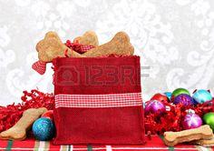 Galletas para perros hechos en casa, en forma de huesos, llenan una bolsa festiva de la Navidad, delicias caseras saludables para un perro