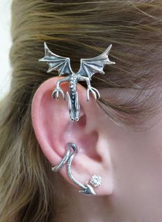 This solid sterling silver, Curious Dragon Ear Wrap sits atop the ear, watching all that is going on. It's tail drops down behind the ear forming the ear wrap and also etwines around to cuff the edge of the ear. It is configured for the right ear only and is an easy, secure and comfortable ear piece to wear. -From Etsy