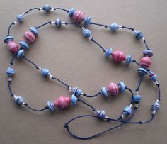 This red and blue paper bead necklace is 39 inches (or 99 cm.) long, and made out of hand painted paper, a film poster and a security envelope. But if you don't tell anyone, I'm pretty sure they would never know! The waxed cotton thread is a dark blue, making the lighter blue paper beads really stand out.
