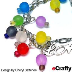 With just a few supplies from eCrafty.com, Cheryl created a fun summery Rainbow Sea Glass LOVE charm bracelet.   Perfect for anyone young at heart.  eCrafty stocks sea glass beads in lots of colors and sizes for your next project.  For instructions and clickable supply list & links, read on! #seaglass #beachglass #seaglassbeads #diy #charms #bracelet #etsy #handmade #rainbow #charmbracelet #summer #love #wedding #summerwedding #diygifts Glass Jewelry, Glass Beads, Diy Crafts Jewelry, Love Charms, Sea Glass, Diy Gifts, Beaded Bracelets, Supply List, Charmed