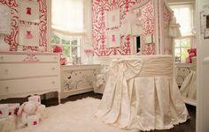 adorable white & pink girl's nursery design with pink damask wallpaper, white chic ribbon round crib, white flokati rug, white vintage dresser chest with pink details, framed dress art and white ribbon roman shade.