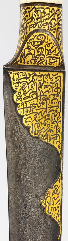 """Persian kard dagger, early 19th century, detail view of the blade decoration, walrus ivory hilt, watered steel blade, gold inlay. Met Museum. The blade and handle of this dagger is inscribed with Qur'anic passages thought to imbue it with talismanic properties believed to offer protection and ward off evil. """"Damascus"""" or """"watered"""" steel refers to blades that have been given a wavy or """"watered"""" pattern, created by specific smelting and crucible techniques prior to forging."""
