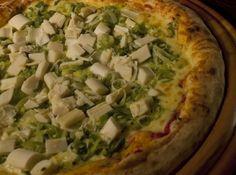 Receita de Pizza Brasileira - 1 tablete (15 g) de fermento biológico fresco, 1 colher (sopa) de açúcar, 1,5 xícara (chá) de água, 500 g de farinha de trigo, 1 colher (chá) de sal, 4 colheres (sopa) de óleo de milho ou azeite, 1 copo de molho de tomate, Orégano a gosto, 60 g de requeijão cremoso, 200 g de mussarela, 150 g de alho-poró refogado, 200 g de palmito picado