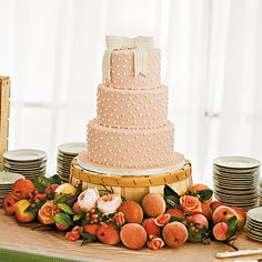 Bow-Topped Peach Wedding Cake | Peaches were used to decorate this three-tiered wedding cake, which was placed on an overturned peach basket.