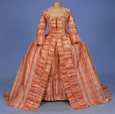 Plais silk Robe a la Francaise, c. 1765. Red, pink and cream taffeta open gown with 3/4 sleeve and U-neck trimmed in self furbelows, back having two double box pleats falling from the neckline flanked by inverted pleats at the waistline. Trained skirt with deep satin hem facing on train, bodice lined in linen, matching petticoat having three front furbelows, upper back panel of linen with waist tie.