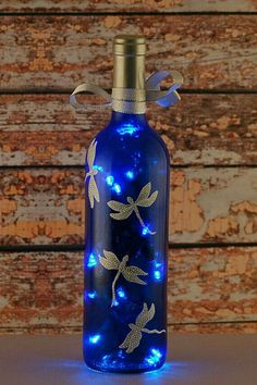 Blue and white dragonfly wine bottle lamp. An empty clear wine bottle was reclaimed and repurposed into this wine bottle light. After cleaning and removing the labels, the clear bottle was tinted a de (Bottle Painting Decor) Recycled Glass Bottles, Glass Bottle Crafts, Painted Wine Bottles, Lighted Wine Bottles, Bottle Lights, Decorated Bottles, Liquor Bottles, Decorative Glass Bottles, Decorate Wine Bottles